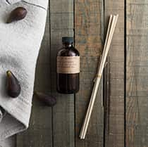 Black Fig scented oil reed diffuser, presented in an apothecary inspired amber jar, with natural rattan reeds. By P.F. Candle Co.