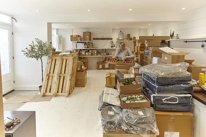 Clare Southcombe-Holmes unpacking her first stock order from Lene Bjerre, Tine K Home, ON Interior and Affari ready for the opening of No64 Biscuit House.